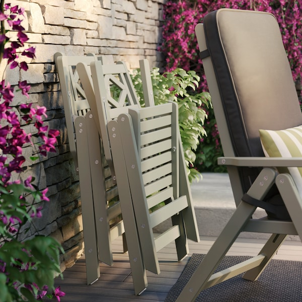Two beige chairs folded up against a brick wall with green trailing plants and purple flowers behind a reclining chair.