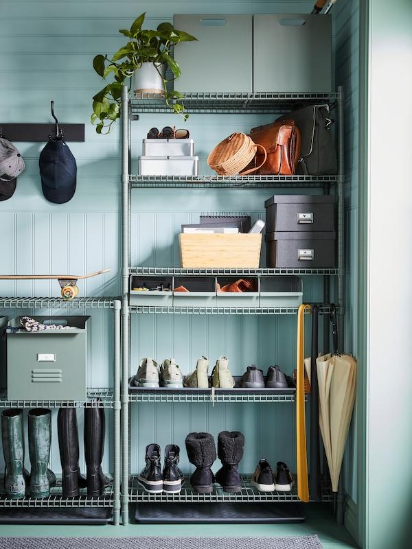OMAR hyllor med lådor, väskor, en krukväxt, skor och andra föremål, står i ett hörn i en hall.