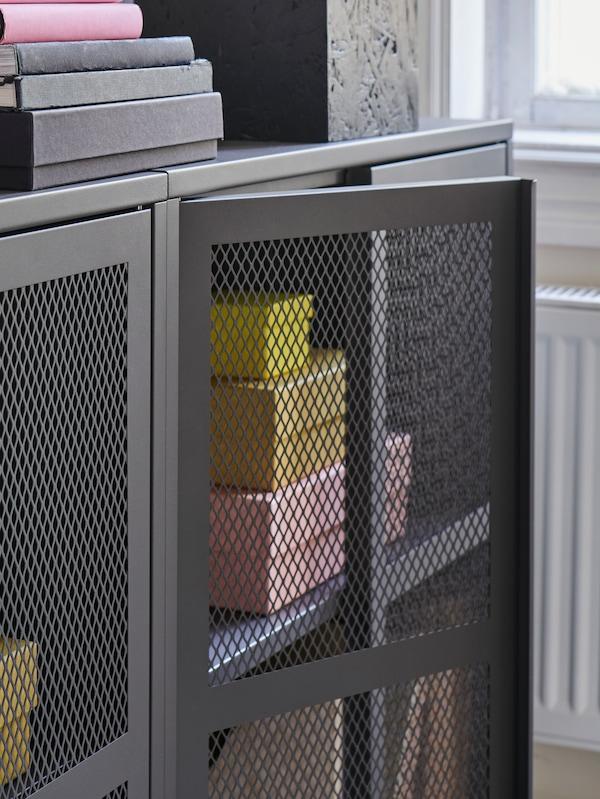 Šedá skříňka IVAR se síťovými dveřmi plná pastelově žlutých, růžových a šedých krabic a knih. Jedny dveře jsou mírně otevřené.