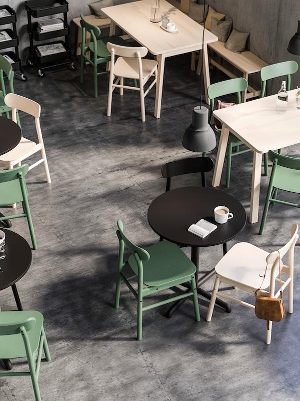 Tavoli quadrati e rotondi, tutti con sedie RÖNNINGE, in una caffetteria illuminata da grandi lampade a sospensione HEKTAR.