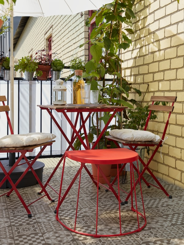Un taburete/mesa auxiliar en rojo, al lado de una mesa y sillas, sirve como asiento adicional para los invitados.