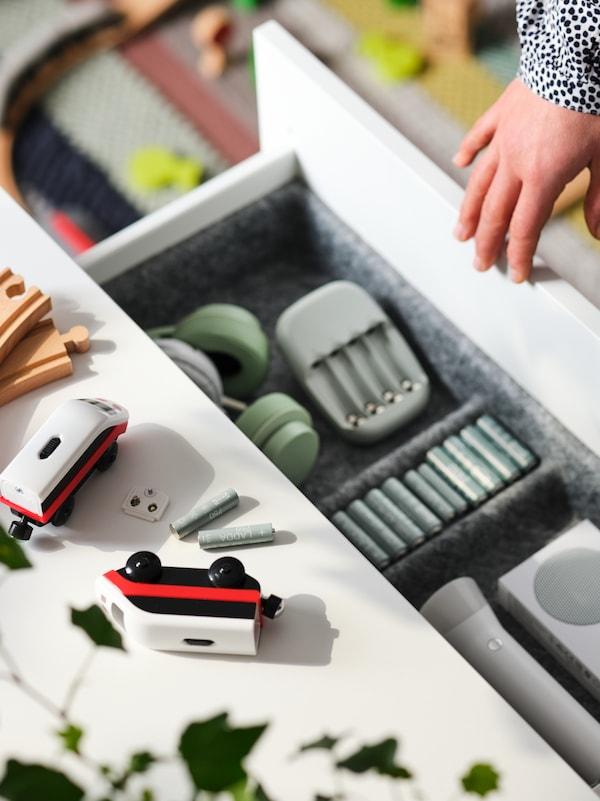 Parti di un trenino elettrico e batterie ricaricabili LADDA su una superficie sopra un cassetto aperto con batterie e altri oggetti.