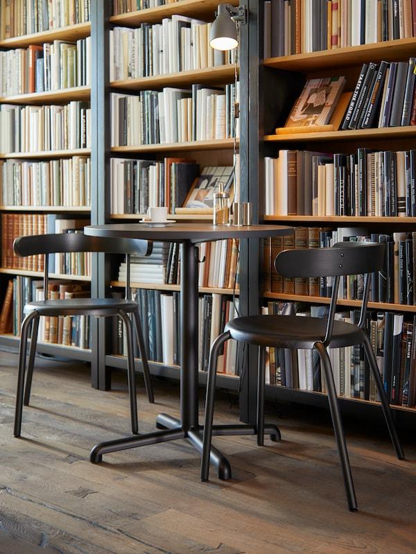 Круглый антрацитовый стол для кафе с крючками под столешницей и два стула, за ними большой книжный шкаф с книгами.