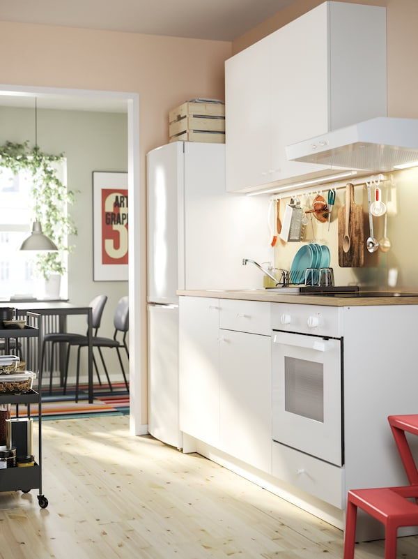 A white KNOXHULT kitchen with base cabinets and a wall cabinet, a fridge and freezer and a dining area in the background.