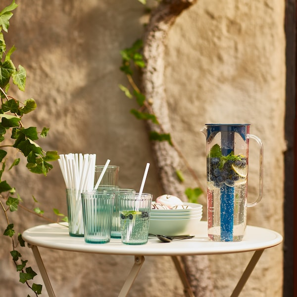 A MOPPA jug, its contents garnished with berries, KALLNA glasses, paper straws and plates placed on a sunlit garden table.