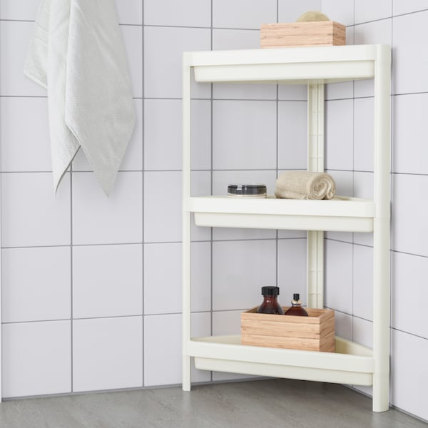 A white-tiled bathroom with a VESKEN corner shelf unit with towels and wooden boxes on the top and bottom shelves.