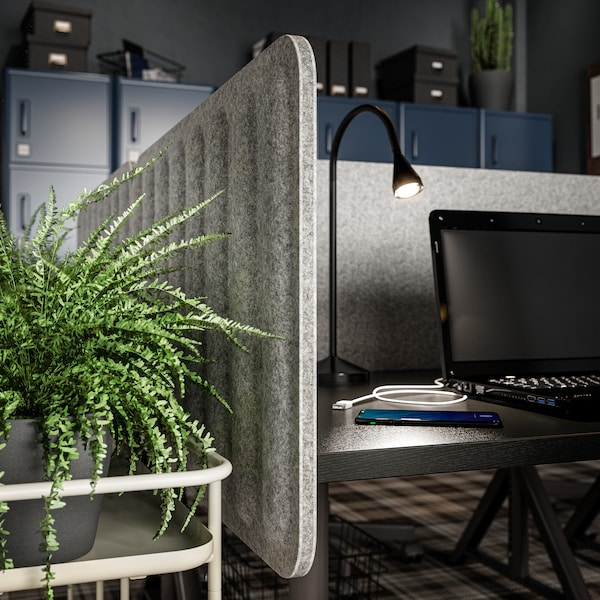 Close-up of a textured grey felt screen on a desk with a black reading lamp and a black laptop on top and a plant next to it.