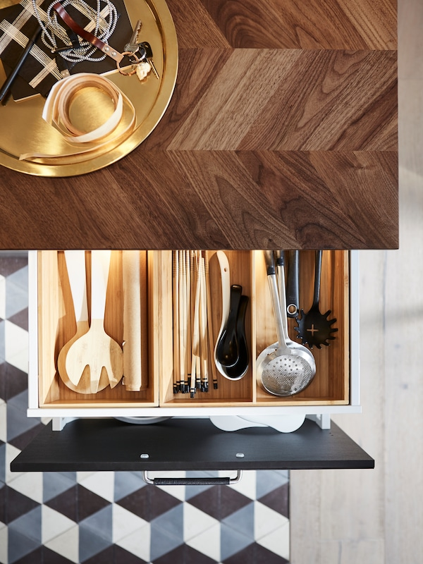 A kitchen with a walnut countertop and an open drawer that has a utensil tray inside to organize the kitchen utensils.