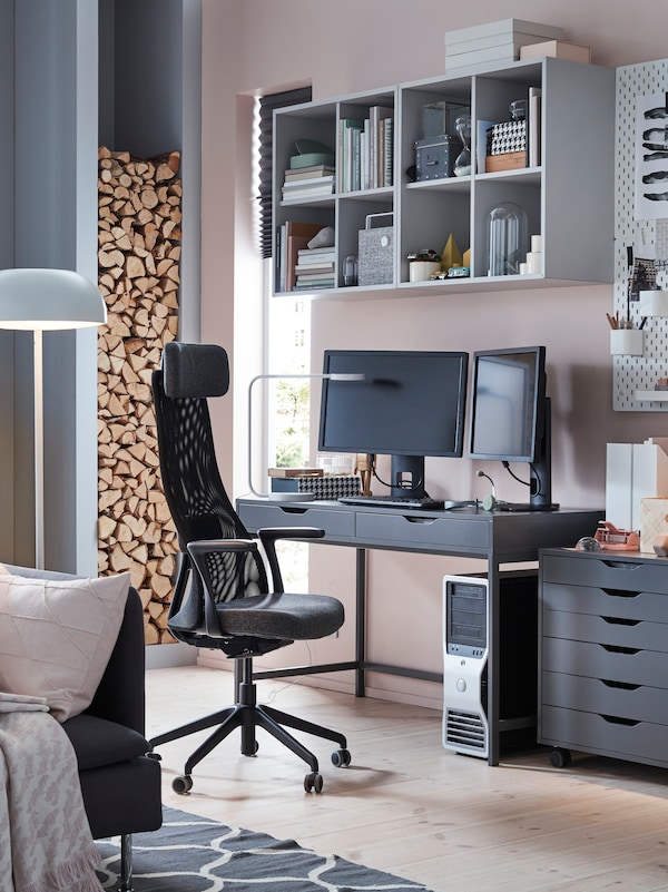 A work area in a living room with a swivel chair in black, a black desk with screens, storage and shelving.