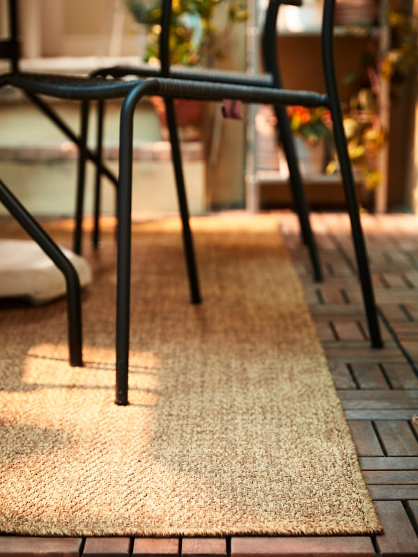 Tapete LYDERSHOLM em fibras, com cadeira preta em cima.