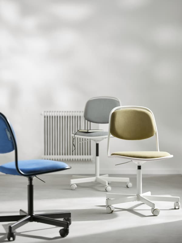 Tre ÖRFJÄLL kontorstoler, én hvit og lysegrå, én hvit og gulgrønn og én svart og blå, i et rom.