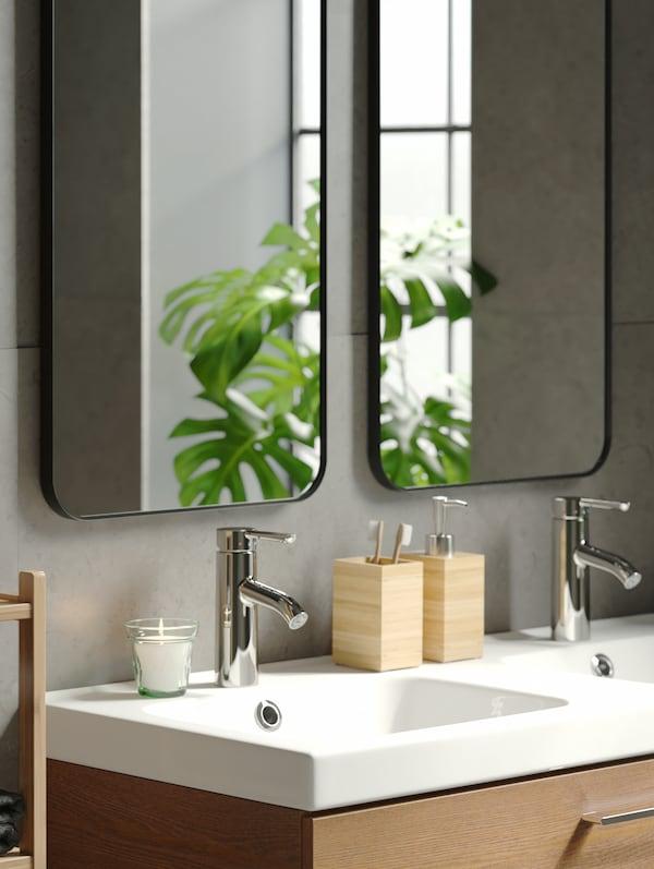 موزع صابون وحامل فرش أسنان DRAGAN من الخيزران على حوض غسل أبيض مع مرآتينLINDBYNمثبتتين فوقه.