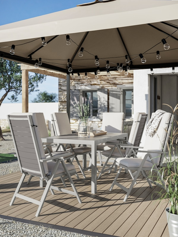 A dining table, outdoor chairs with cushions, wood-like decking, a grey-beige gazebo with hanging light chains.