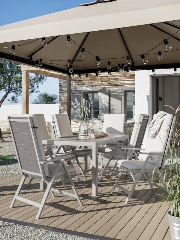 Ein Esstisch, Outdoor-Stühle mit Polstern, Bodenrost in Holznachbildung und ein grauer Pavillon mit Lichterketten.
