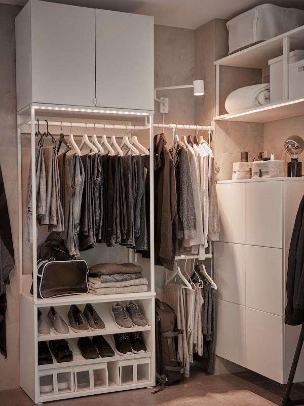 Ein weisser PLATSA Kleiderschrank mit Kleiderstangen, Schuhaufbewahrung, Lichtleisten und Boxen, u. a. mit einer weissen PLATSA Wandaufbewahrung.