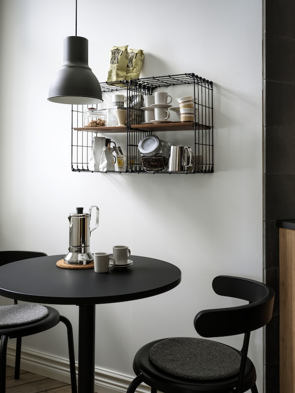 Two GULLHULT wall shelves holding coffee and tea accessories hang above a small, round table and two chairs.