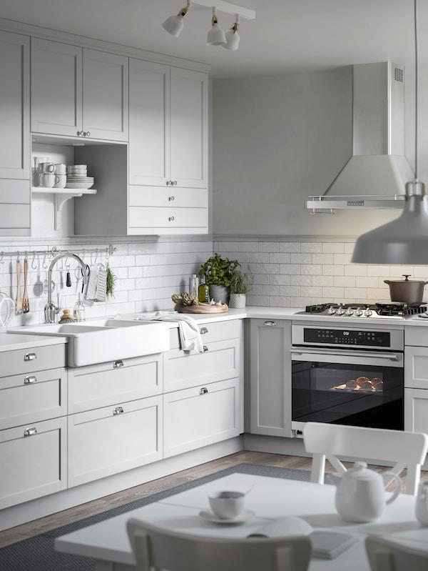 Två ljusgrå köksskåp med ljusgrå luckor, vit bänkskiva med två växter, ljusgrå lådfronter nedanför.