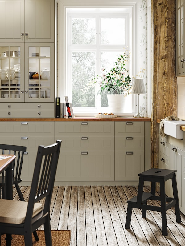 Cucina in stile tradizionale con pavimento in legno, frontali e mobili STENSUND beige e piano di lavoro SÄLJAN effetto rovere.