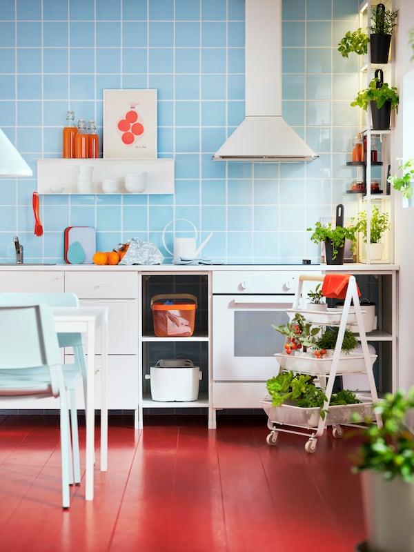 Parete piastrellata di azzurro con cucina ENHET bianca, scaffali ENHET, carrello RISATORP, tavolo, erbe aromatiche e conserve.