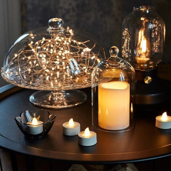 Eine weisse Kerze in einem Glashalter, unter einer Glaskuppel, auf einem Tisch neben anderen LED-Kerzen.