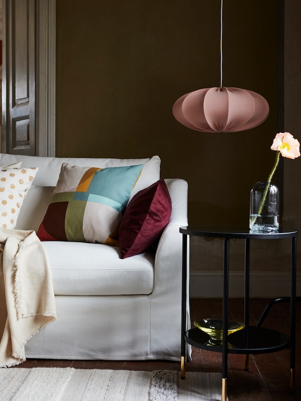 A white sofa with cushions and a blanket, a handwoven rug, a black side table with a vase and bowl, and a pendant above.