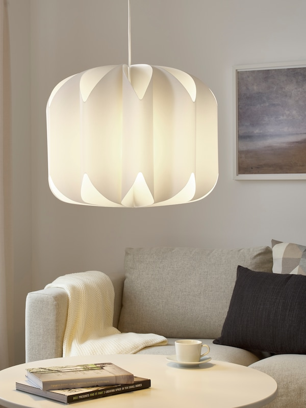 A white pendant lamp shade hangs low above a coffee table with a coffee cup, saucer and books on top and a sofa behind.