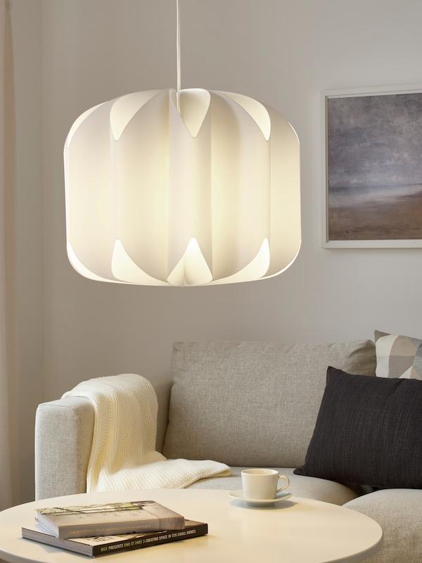Biela závesná lampa nad konferenčným stolíkom so šálkou kávy a knihami, sivá pohovka s vankúšmi v pozadí.