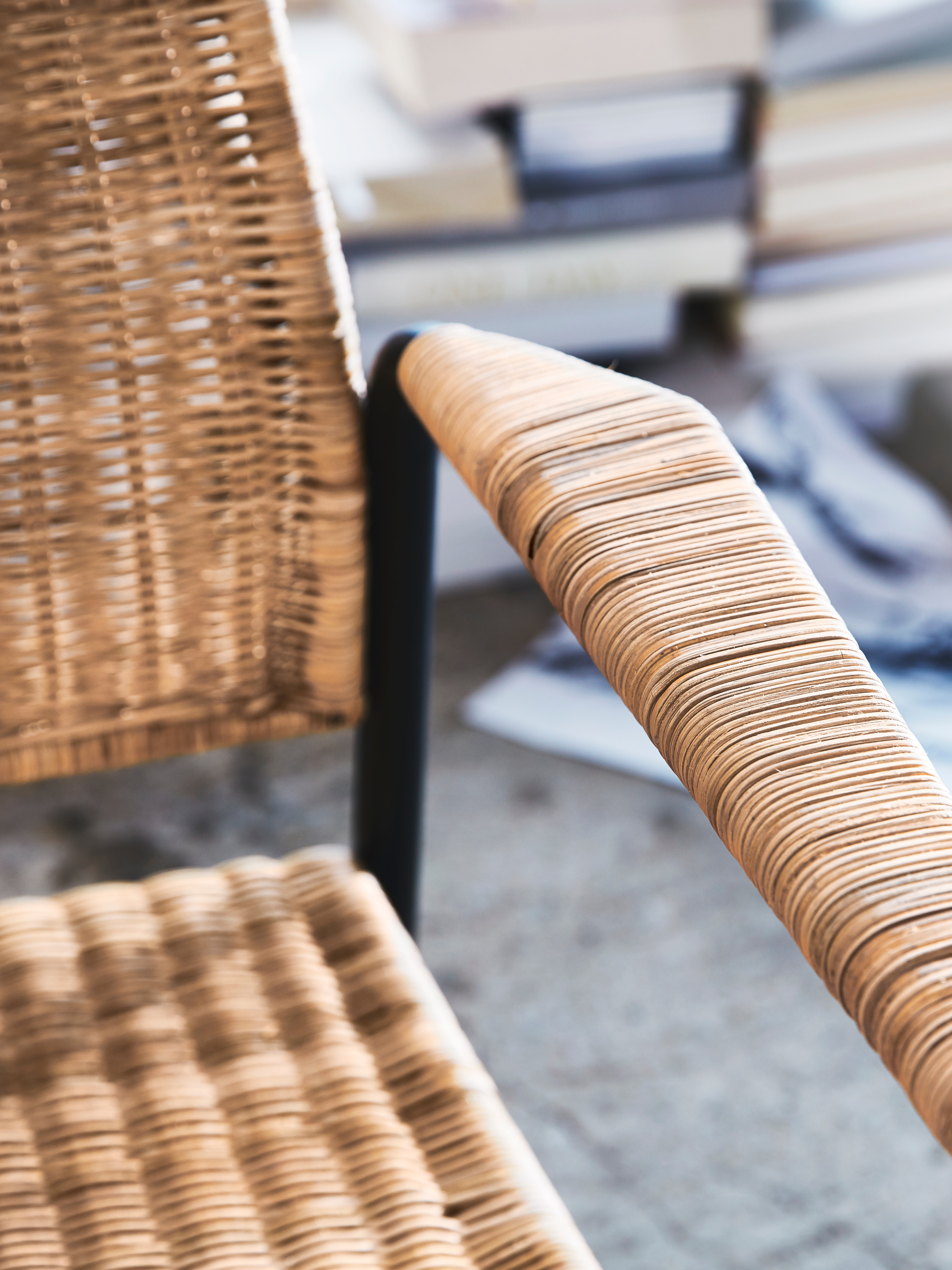 A close-up of the back, seat and armrest of ULRIKSBERG armchair in rattan/anthracite, showing rattan on a coated-steel frame.