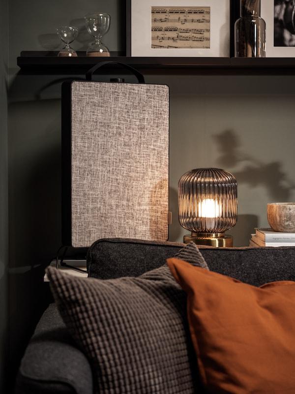 De SOLKLINT tafellamp in messing/grijs op een ladekast met daarnaast de FÖRNUFTIG luchtreiniger tegen een wand in de woonkamer.