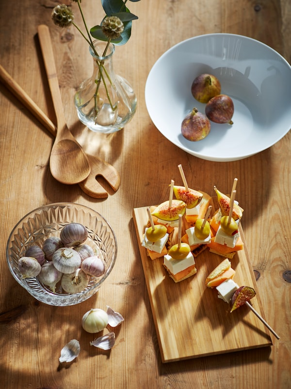 Canapés on sticks on an APTITLIG chopping board, figs in an OFTAST bowl, and decorations on a wooden table.