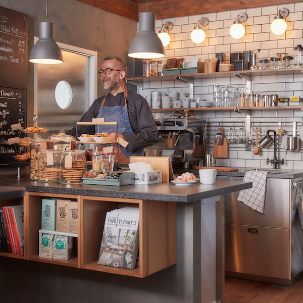 The counter of a cafe, lots of food items displayed on it, a man stands behind the counter, with shelves behind him.