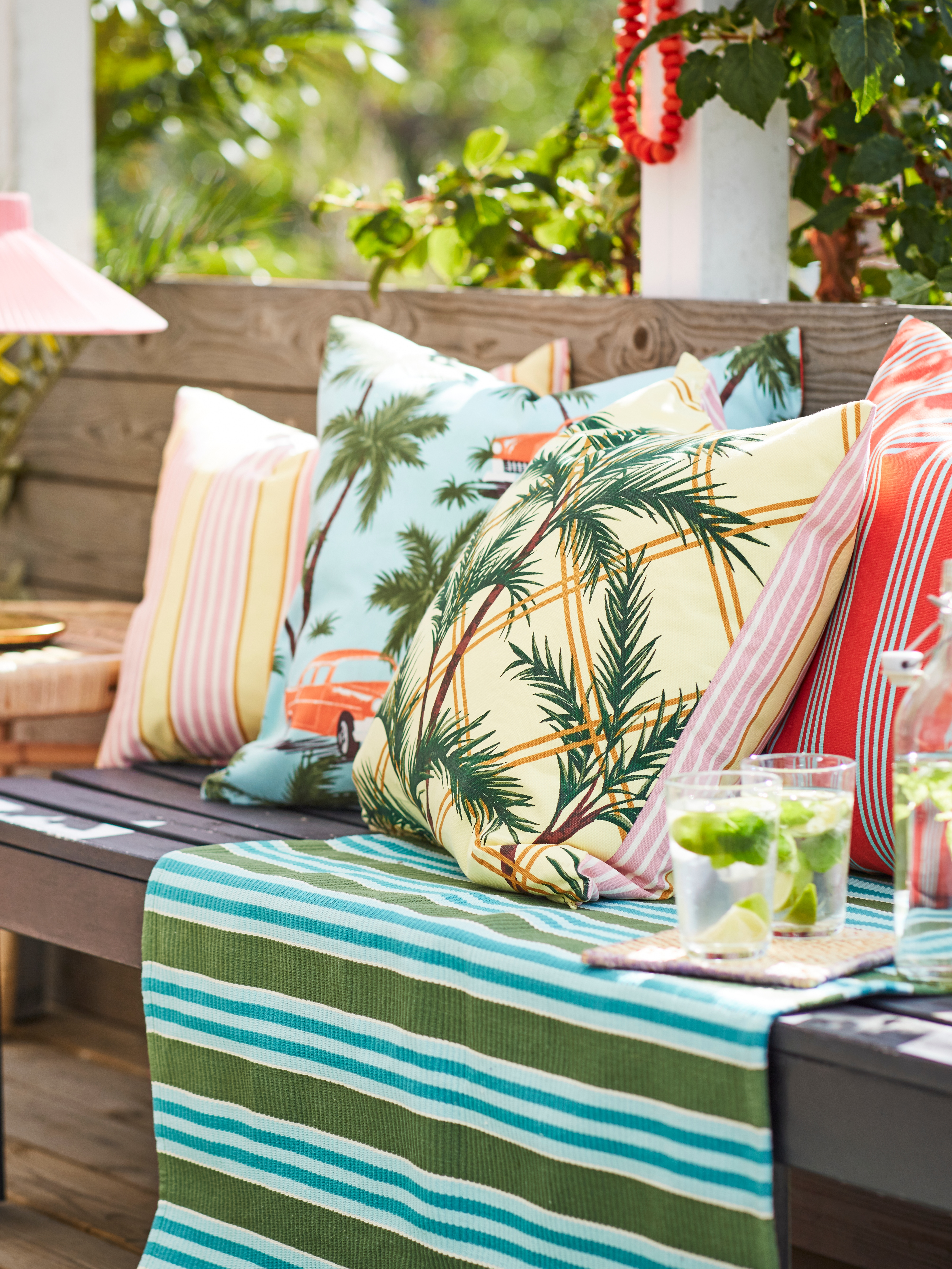 An outdoor bench has many cushions, including a SOMMAR 2020 blue/multicolour cushion cover with palm trees and vintage cars.