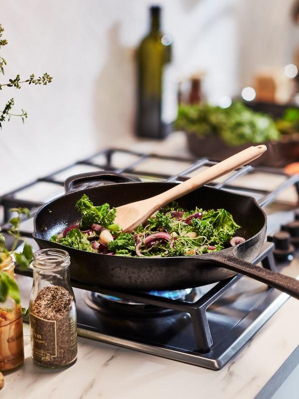 가스레인지 위에 VARDAGEN 바르다겐 주물 프라이팬이 올려져 있고 그 안에 야채와 나무 스푼이 있는 모습.