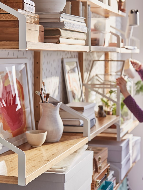 A girl's hands open the lid of a mini greenhouse that sits with books and other objects in a SVALNÄS shelf combination.