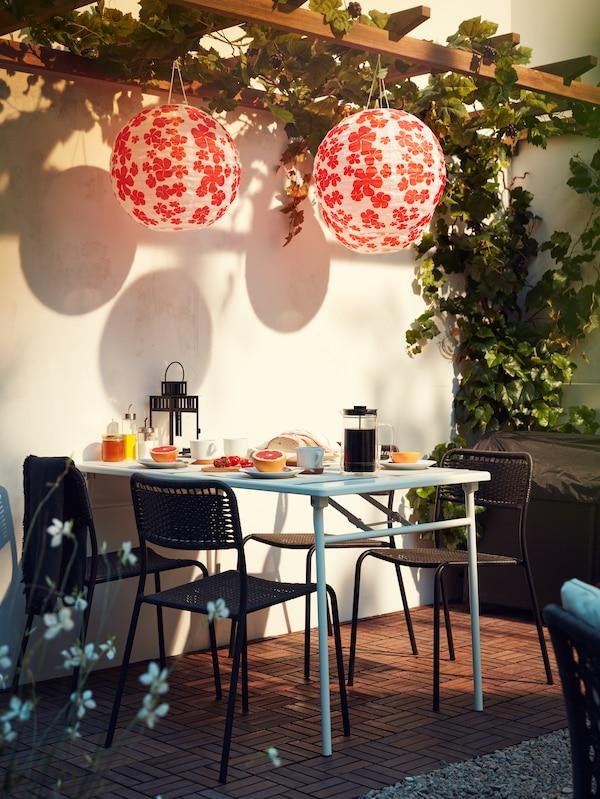 Papierlaternen mit Blütenmuster über einem Tisch, der zum Frühstück eingedeckt ist, Drumherum sind vier stapelbare Stühle zu sehen.