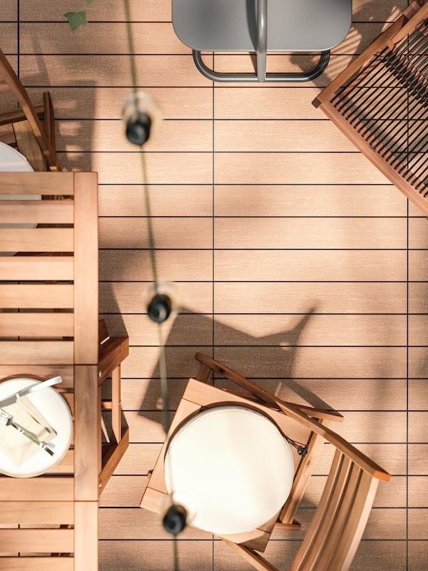 Pardoseală cu aspect de lemn, cu un set de exterior din lemn pentru servirea mesei, șezlong din lemn și o măsuță de cafea.