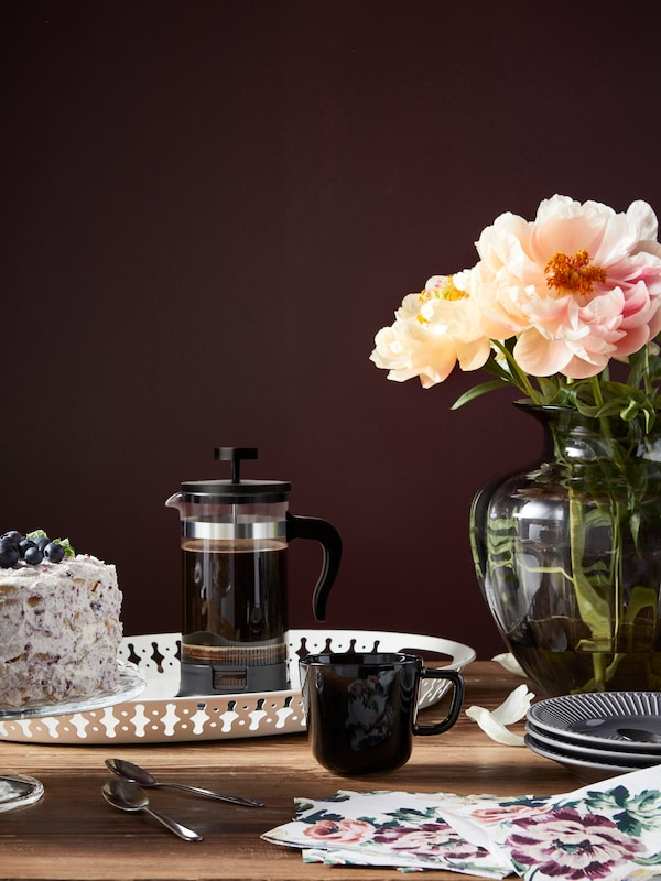 A  coffee press and black mug on a wooden table, beside a glass vase of peach flowers.