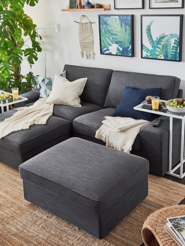 A KIVIK two-seat sofa and two, KIVIK footstools in anthracite colour, pushed together to create a double chaise longue.