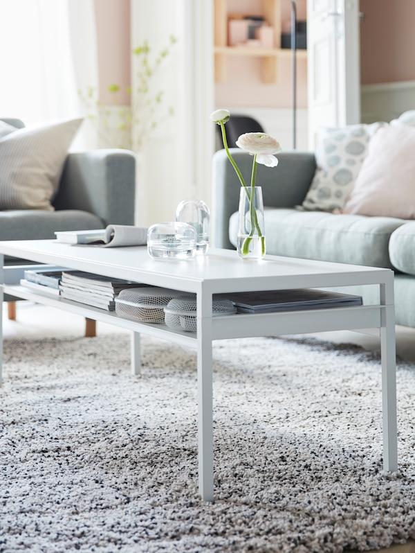 IKEA NYBODA long white coffee table with books stored underneath on a thin, slim shelf.