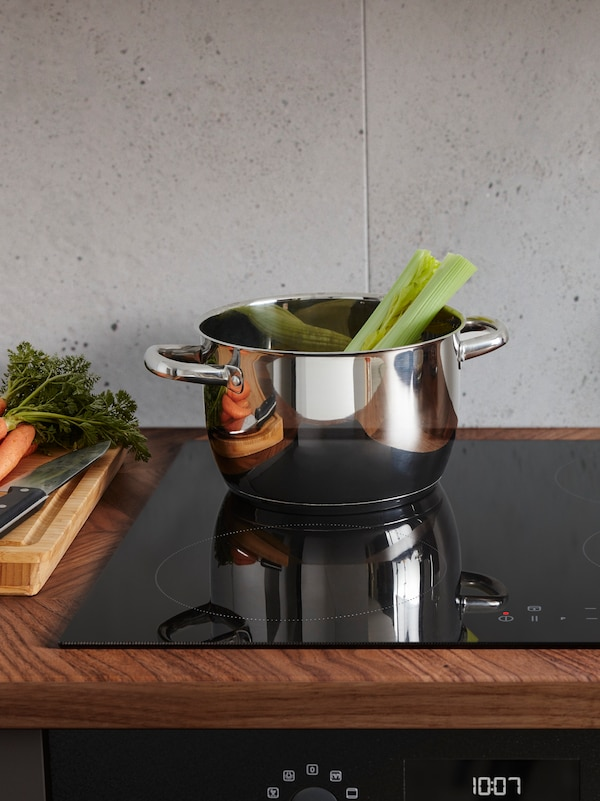An OUTMBÄRLIG pot in stainless-steel containing celery stalks on a black hob next to some carrots on a chopping board.