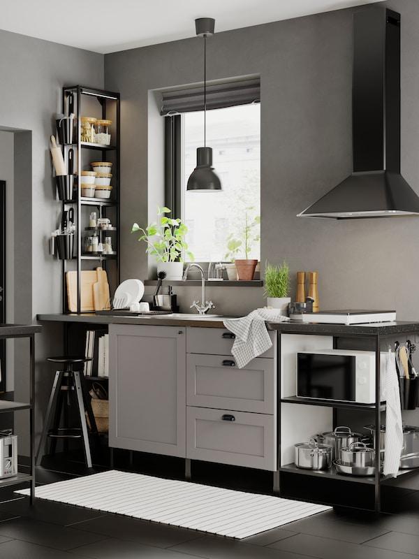 Et ENHET køkken med grå fronter og stel i antracit/grå. Glas og krydderier står på hylder ved siden af et vindue.