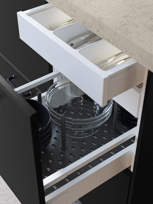 Eine geöffnete schwarze Küchenschublade zeigt Schüsseln in einer UPPDATERA Lochplatten-Organisation in Anthrazit.
