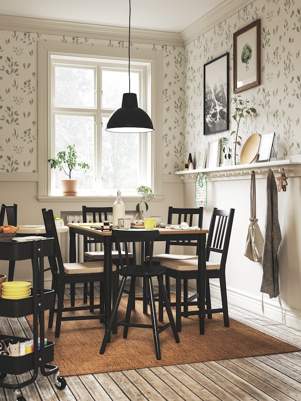 White and green leaf wallpaper, a black dining set, a black junior chair, a black pendant lamp, and a window.