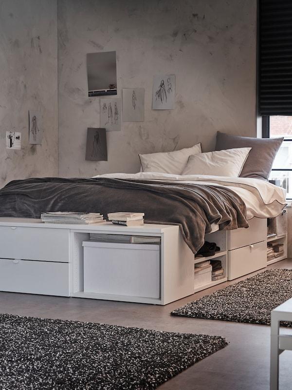 Ein Schlafzimmer mit einem weissen PLATSA Bettgestell mit Schubladen, Ablagen und einer Bank steht an einem Fenster mit einem dunkelgrauen Rollo.