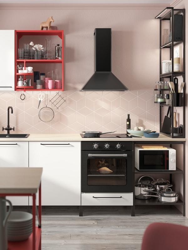 Una cucina con strutture ENHET nere e rosse, un mix di soluzioni a giorno e con ante, frontali bianchi e maniglie nere.