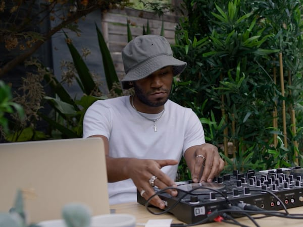 DJ Kaytranada in front of his mixing desk, wearing a white t-shirt and green bucket hat.