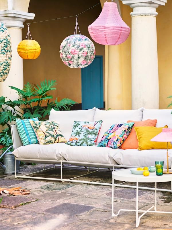 En gårdhave med en udendørs sofa i loungestil og med en masse farverige puder på.