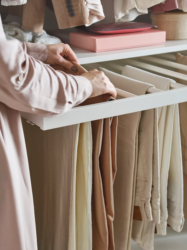 A person going through pairs of trousers hanging on a KOMPLEMENT pull-out trouser rail. A shelf is above it.