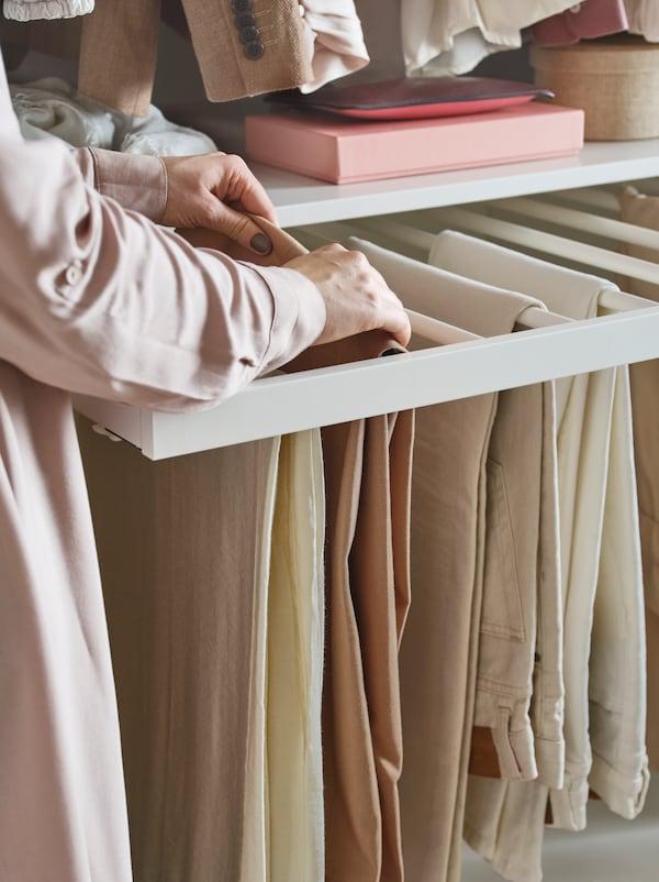 Una persona revisa unos pantalones colgados en un perchero extraíble KOMPLEMENT. Hay un estante sobre él.