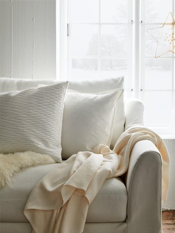 하얀 소파와 쿠션, 담요로 꾸며진 화사한 거실의 모습